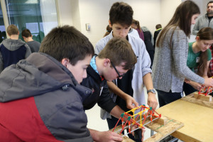 High school visitors work on their bridge building skills